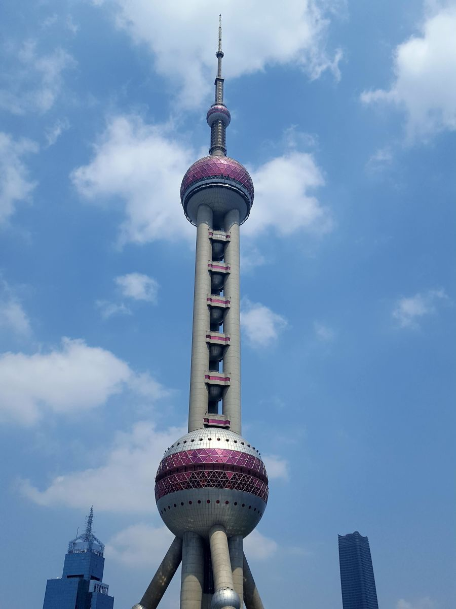 The Oriental Pearl Tower against a blue sky.  A high-speed elevator shoots customers to the top of the tower where they can take in the views of the city.