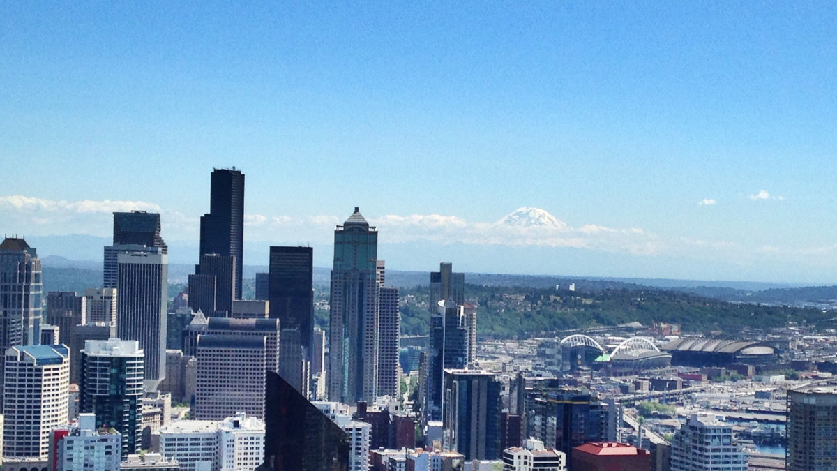 View from the Space Needle in downtown Seattle with Mt. Rainier stick up above the clouds on the horizon.