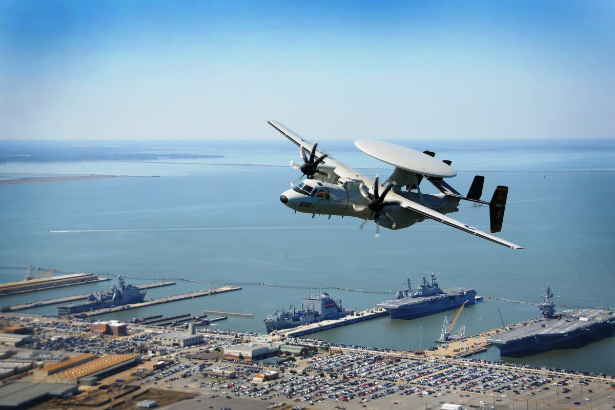An E-2D Hawkeye flies over Naval Base Norfolk in Norfolk, VA