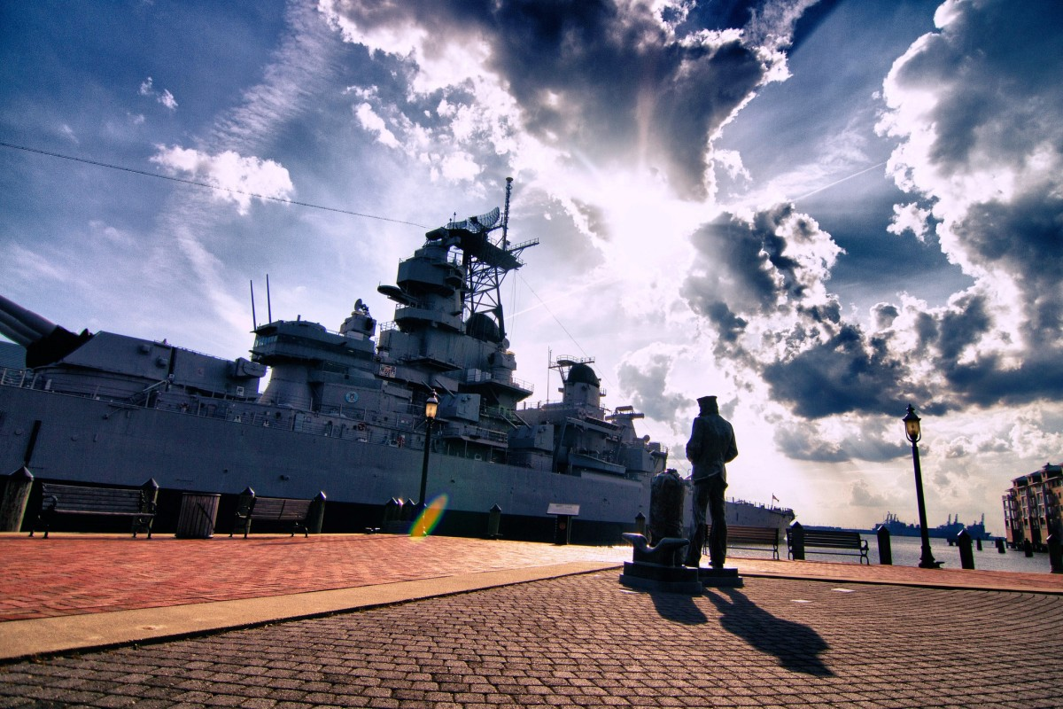 The Lone Sailor statue and the Battleship Wisconsin in Norfolk, VA
