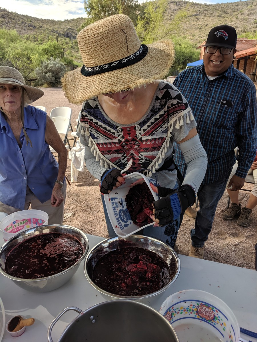 Returning from the desert with the fruit we had harvested.  My wife pours the fruit we gathered into communal pot for the syrup.