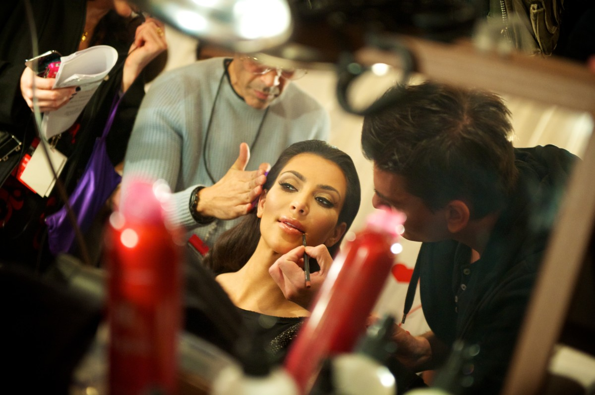 Here, a celebrity, Kim Kardashian is getting her makeup done so she will look up to par with what everyone expects her to look like.