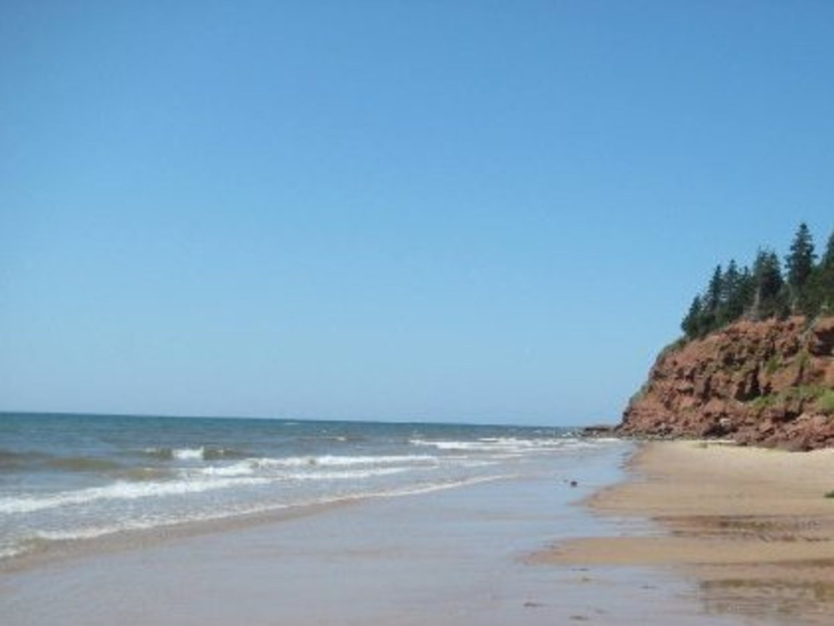 Beach nestled between red rock cliffs in PEI