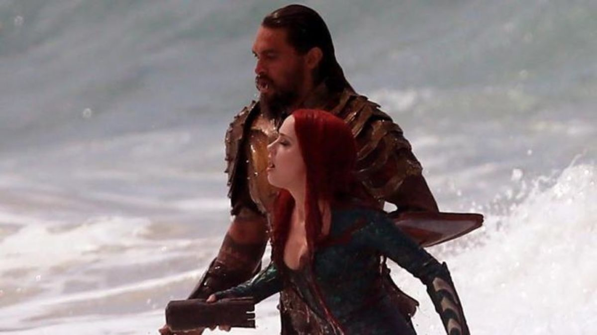 Jason Mamoa and Amber Heard in Aquaman emerge from the ocean.