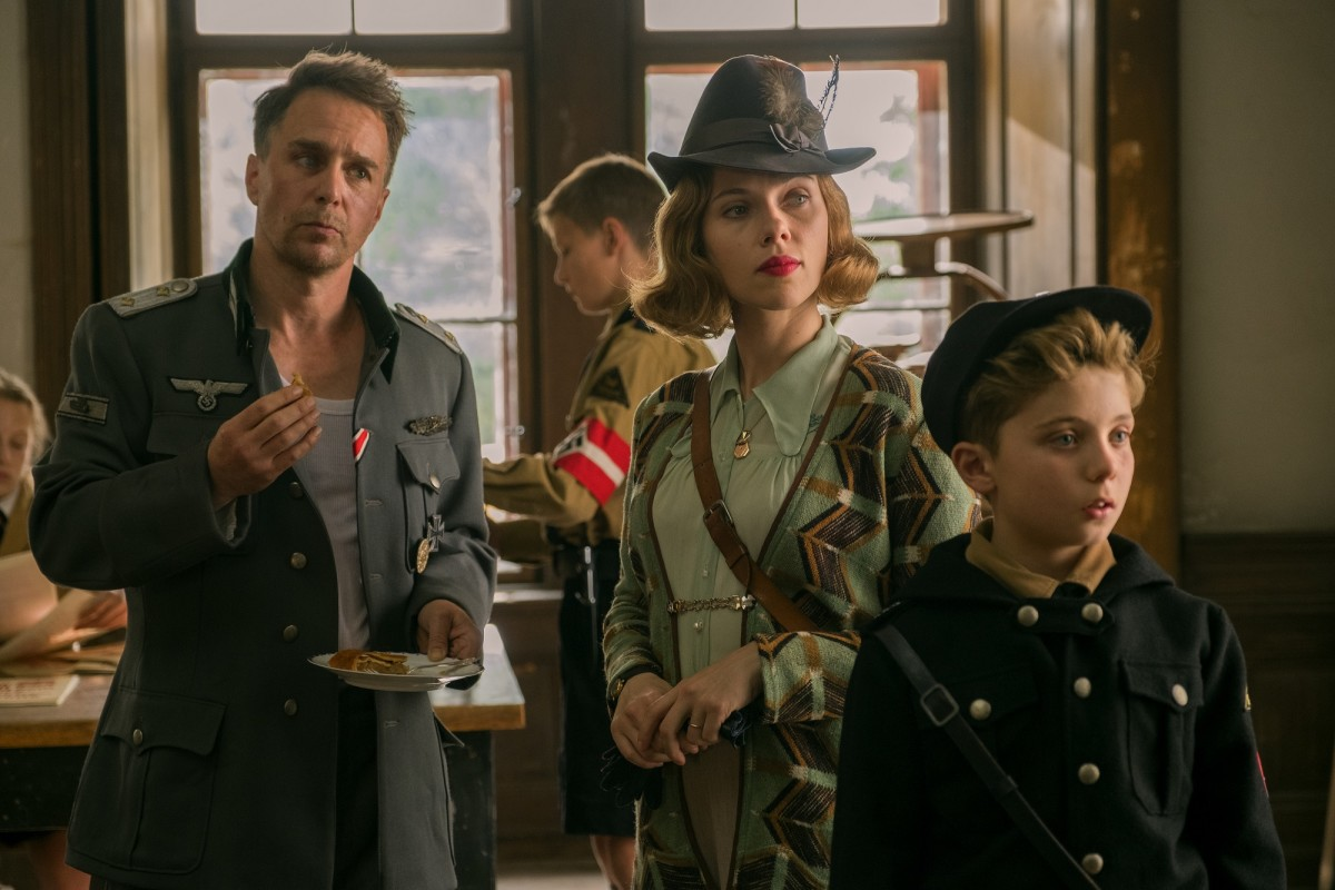 "Sam Rockwell, Scarlett Johansson, and Roman Griffin Davis in, ""Jojo Rabbit."""