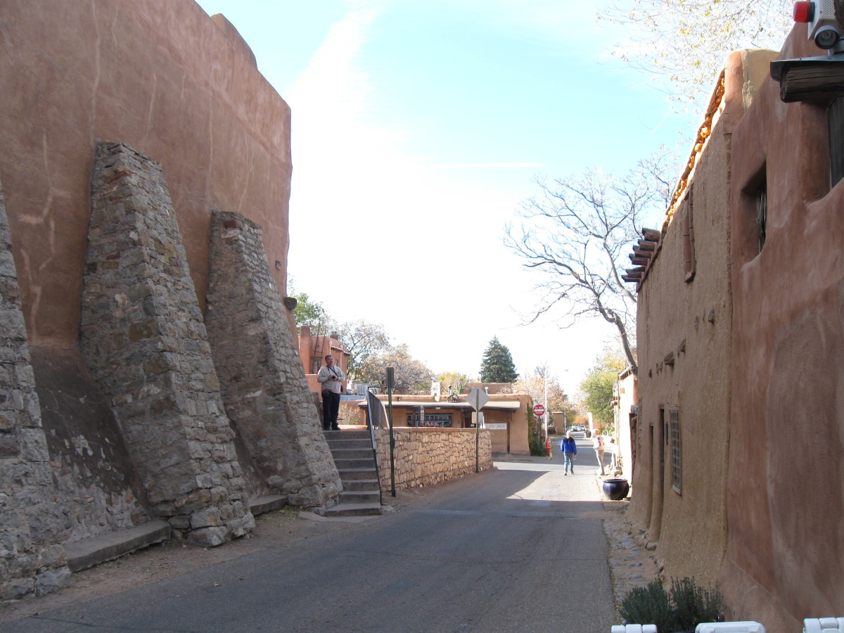 Looking down de Vargas St with Oldest House on the right and rear side of San Miguel Church on the left
