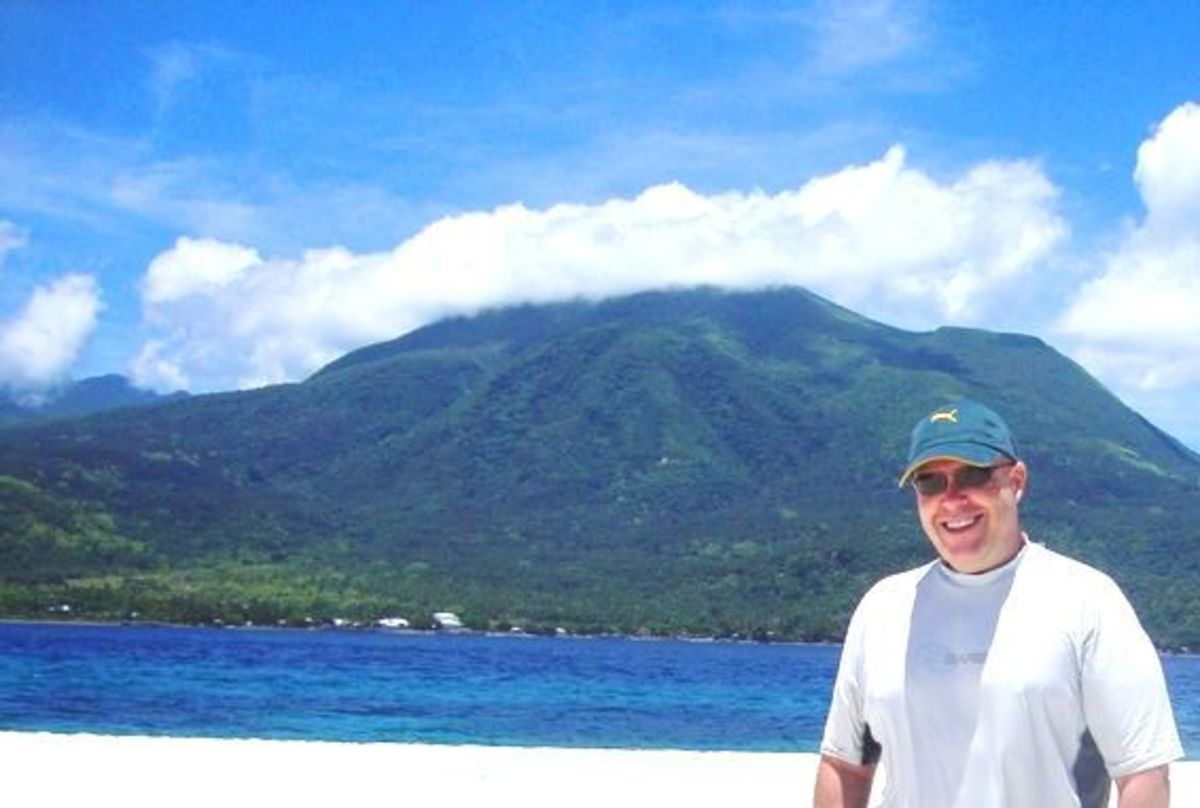 This is a photo of me after I went scuba diving at White Island, with Camiguin Island in the background.