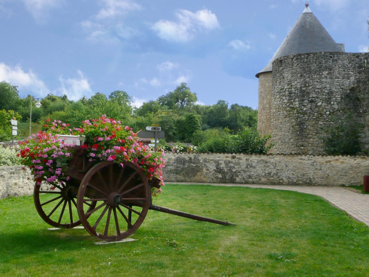 An old wooden wagon, filled with flowers, sits near the gate of Sierck.