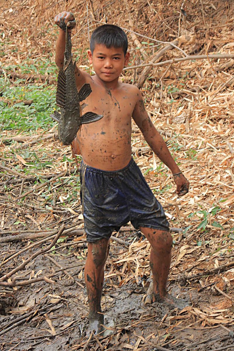 One of the children triumphantly holds his fish catch after the village fish pool is drained