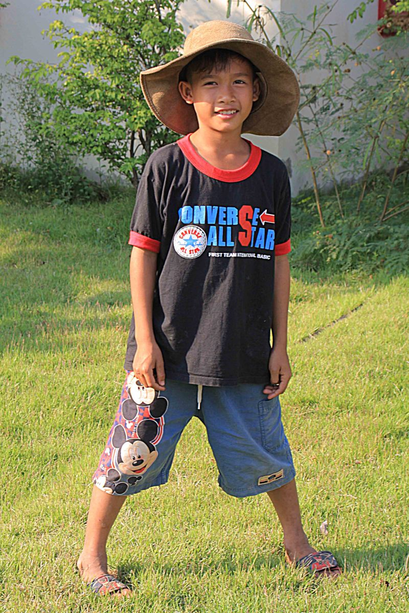 Alisa's brother 'Lucky' in the grounds of the temple, wearing my oversized hat while I took my photos