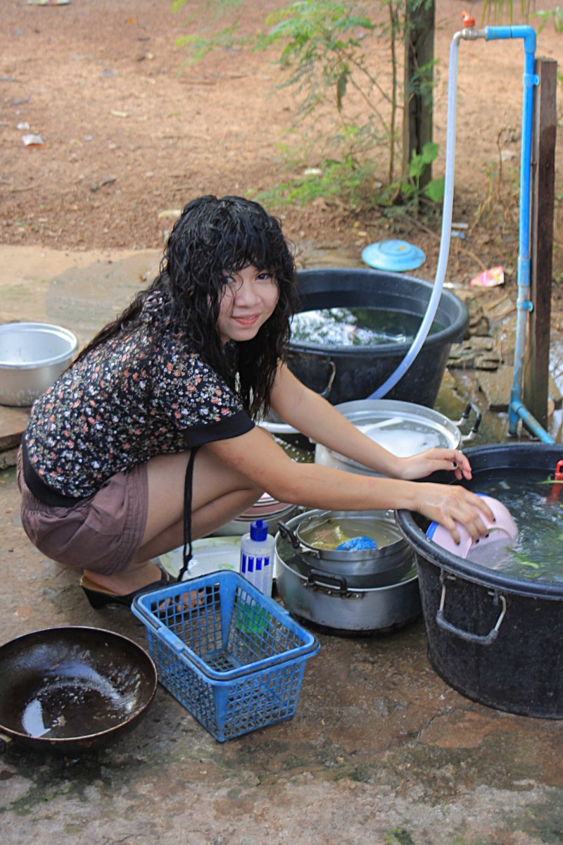 Alisa does the daily chore of dish washing. Water isn't a problem; but hot showers require a kettle!