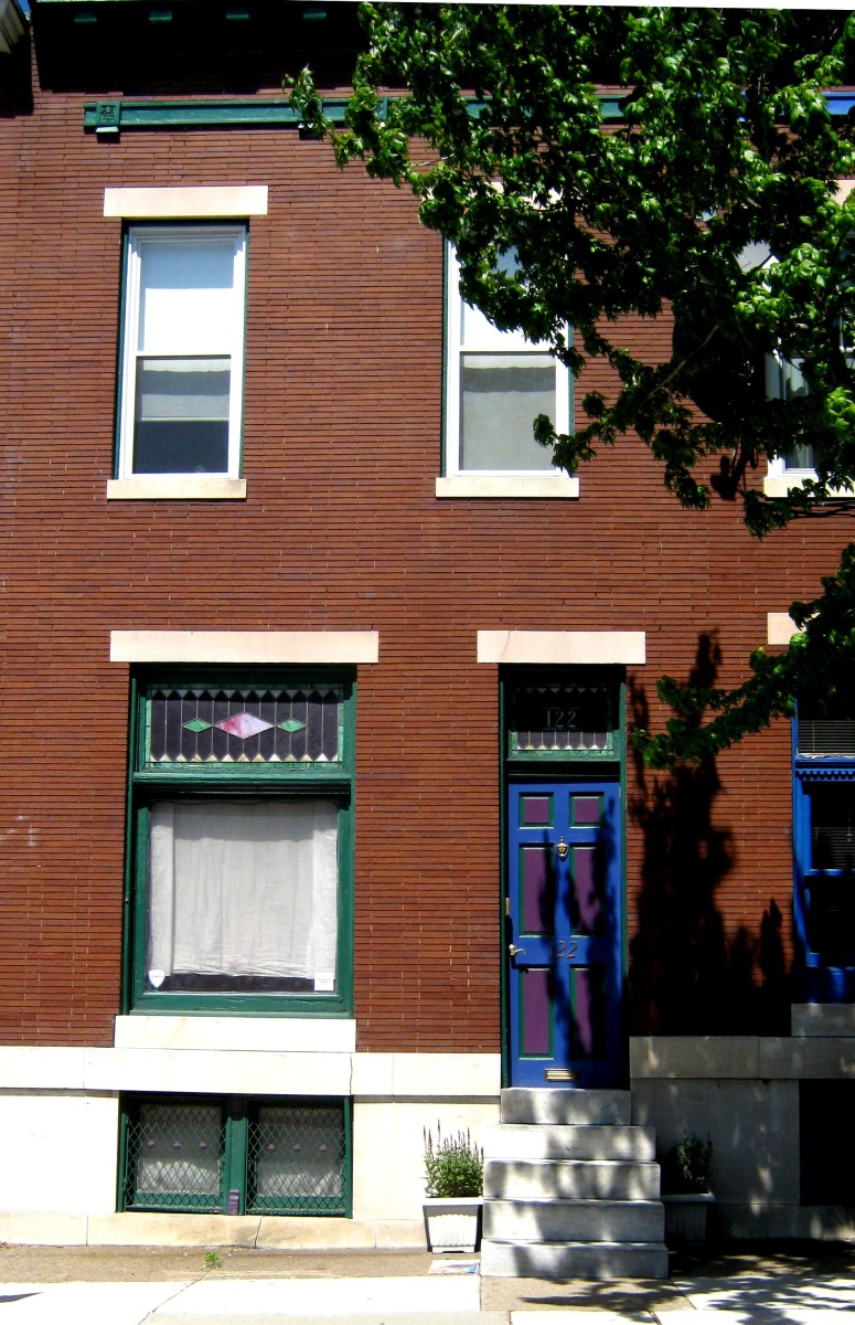 This 2 bay, 2 story rowhouse still has its stained glass above the window and front door.