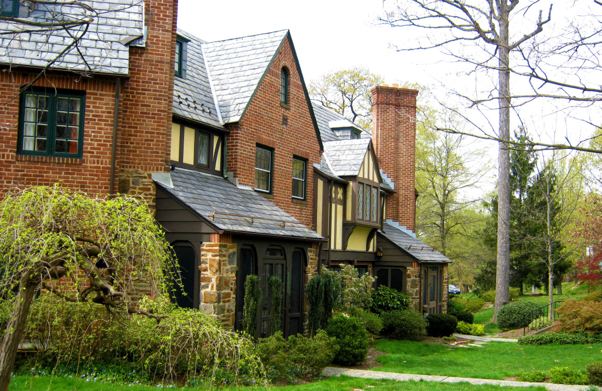 Slate roofs and varied building materials including half timbering in a beautifully landscaped setting.