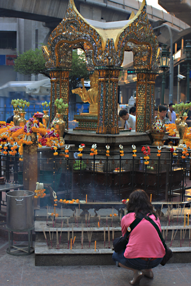A girl prays in front of the shrine. The smoke from the incense is clearly visible as a blueish haze. Top of the picture is the concrete support of the overhead skytrain - the sounds of the metropolis are so close