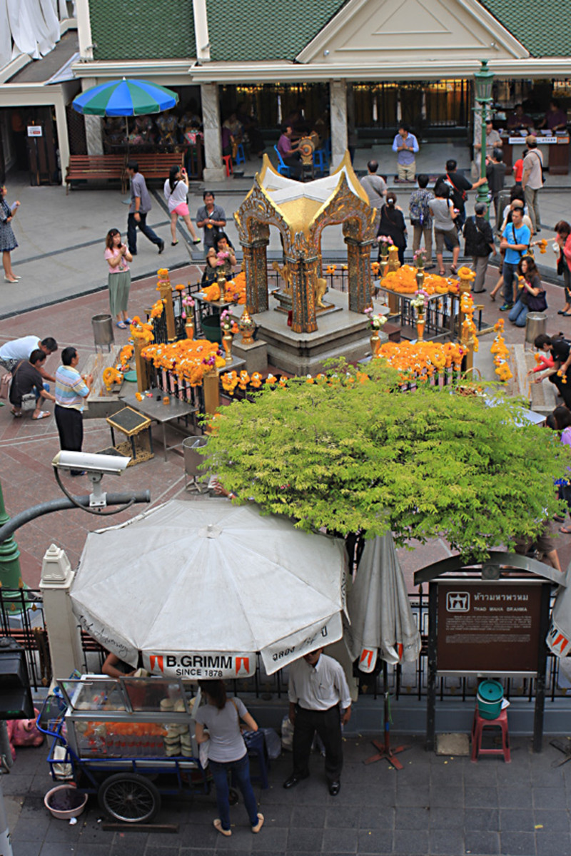 The shrine in the forecourt of the Grand Erawan Hotel, with street vendors in the foreground and the hotel entrance behind