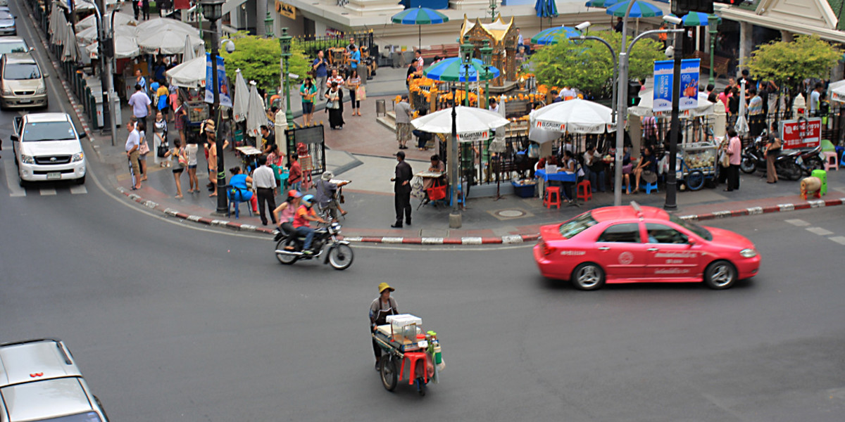 The ancient religious traditions of the Erawan Shrine top of picture, and the busy traffic of the 21st century metropolis in the forground