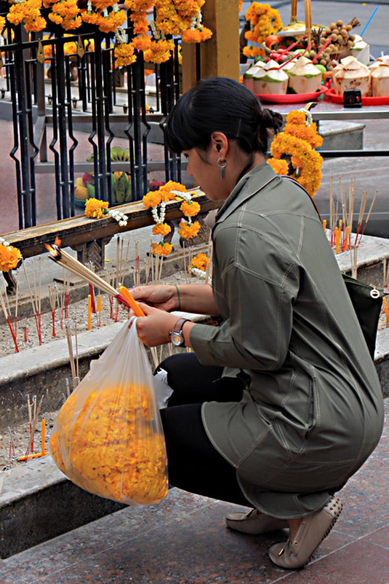 A Thai woman with offerings of flowers and with sticks of burning incense