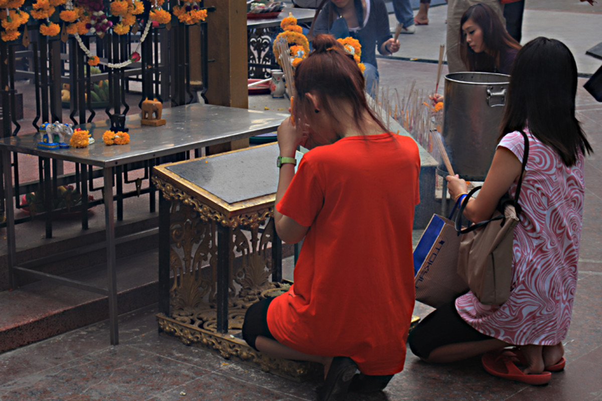 Incense and prayers at one of the four faces of Phra Phrom