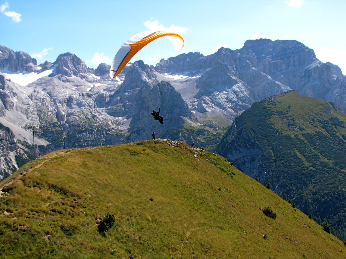 Paraglider taking off in front of the Brenta Dolomites
