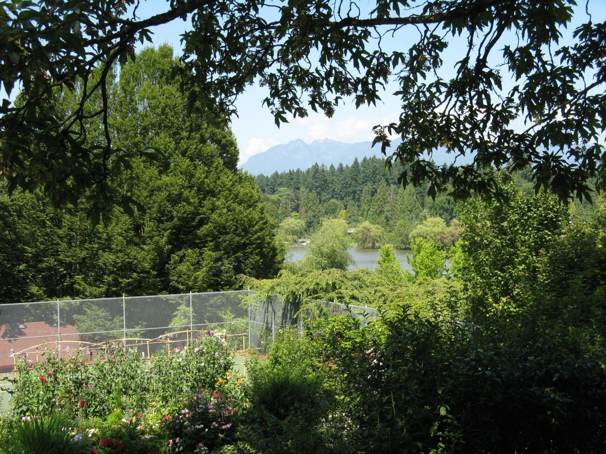 The tennis courts at the end of Robson Street; part of Lost Lagoon and the North Shore Mountains  can be seen in the background