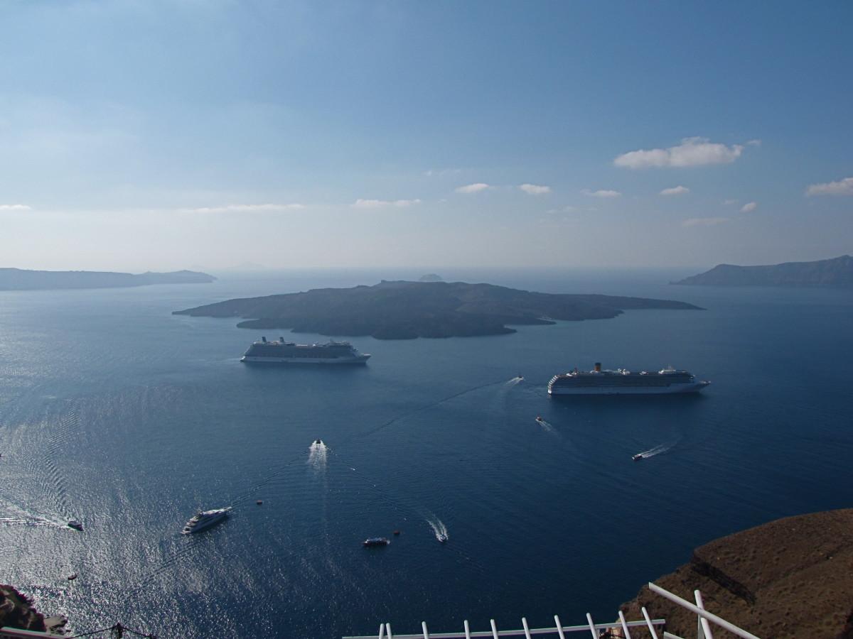 Cruise ships anchored in the caldera with Nea Kameni behind them.