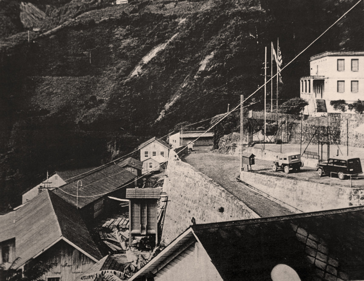View to left of mill site, showing US Consulate at upper right, with flags.