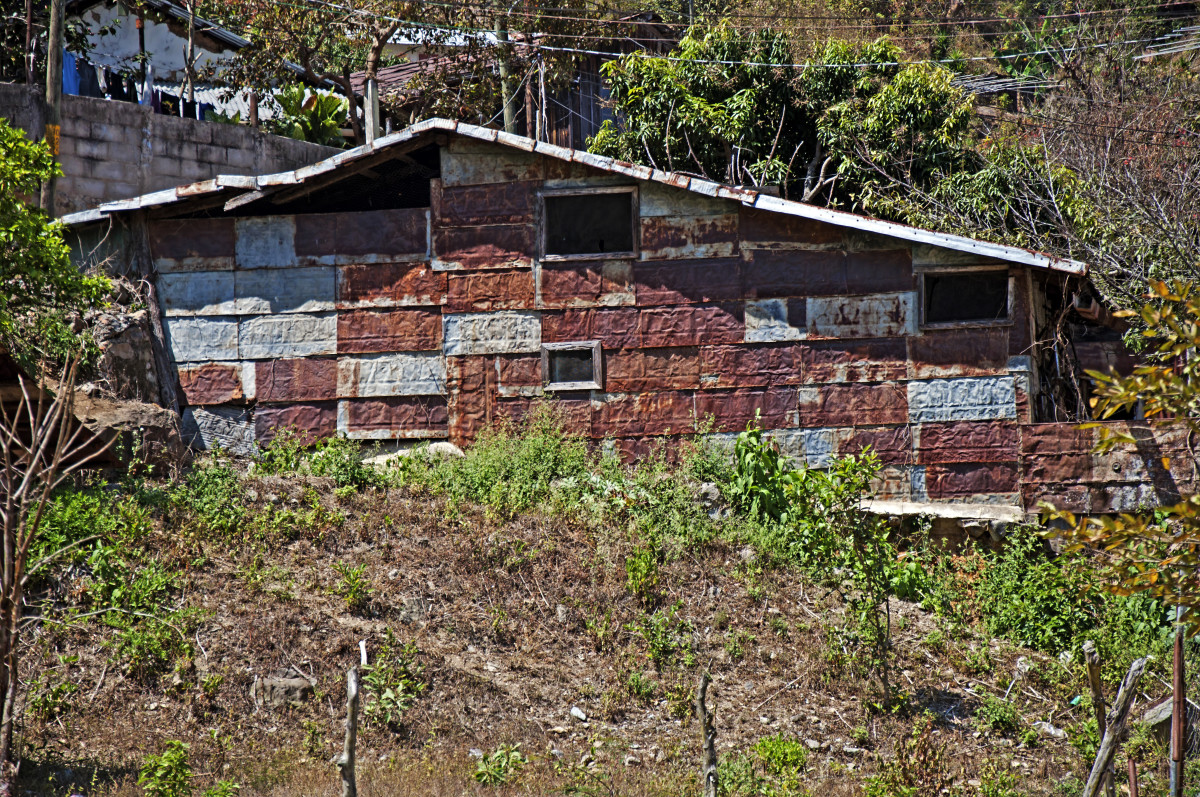 Abandoned dwelling that has been repaired with explosive-barrel siding.