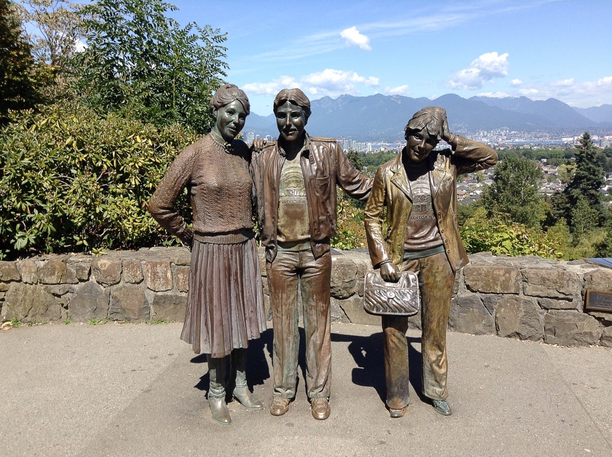 Photo Session is a life-size bronze sculpture of a man photographing three people. Vancouver and a city on the other side of Burrard Inlet are visible in the background.