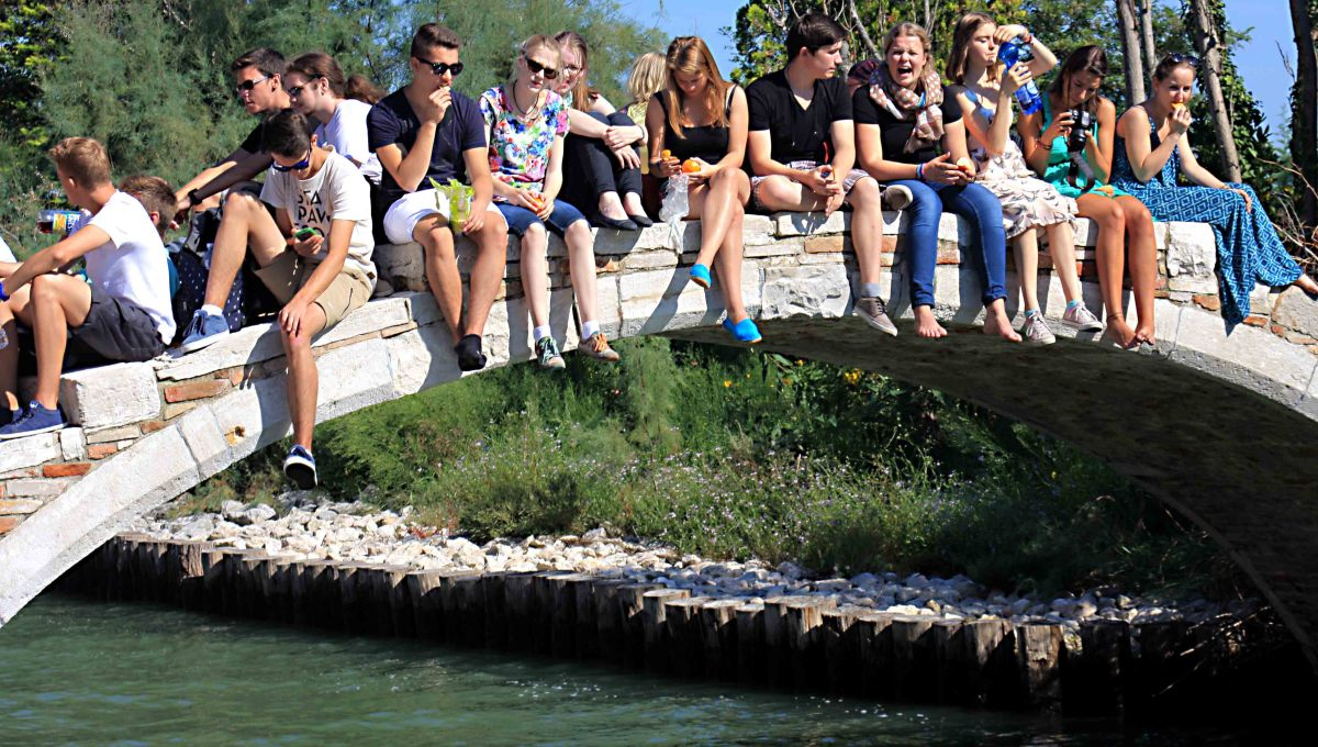 A group of young visitors rests on the Devil's Bridge on the Island of Torcello