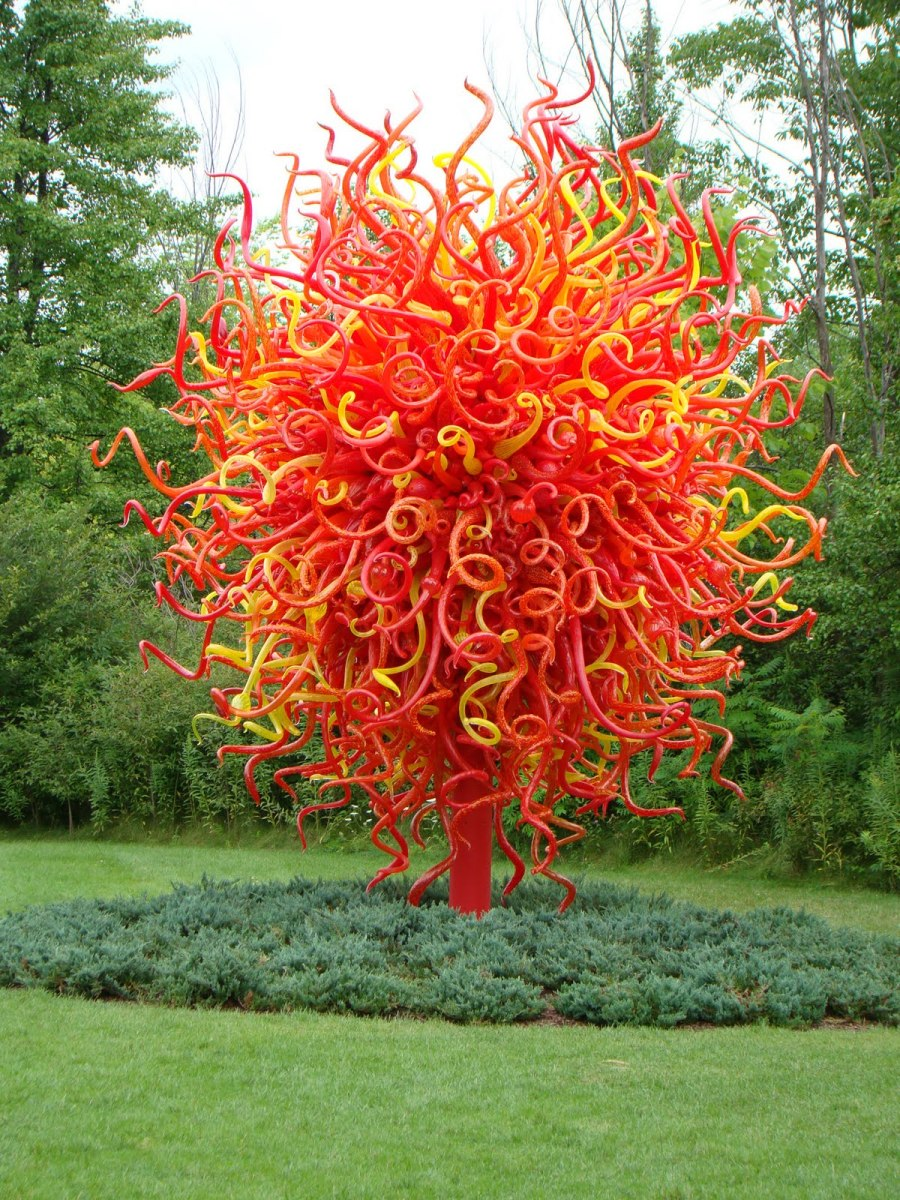 """This flowering tree sculpture - """"Summer Sun"""" consists of 2,000 red, yellow, and orange hand-blown elements."""
