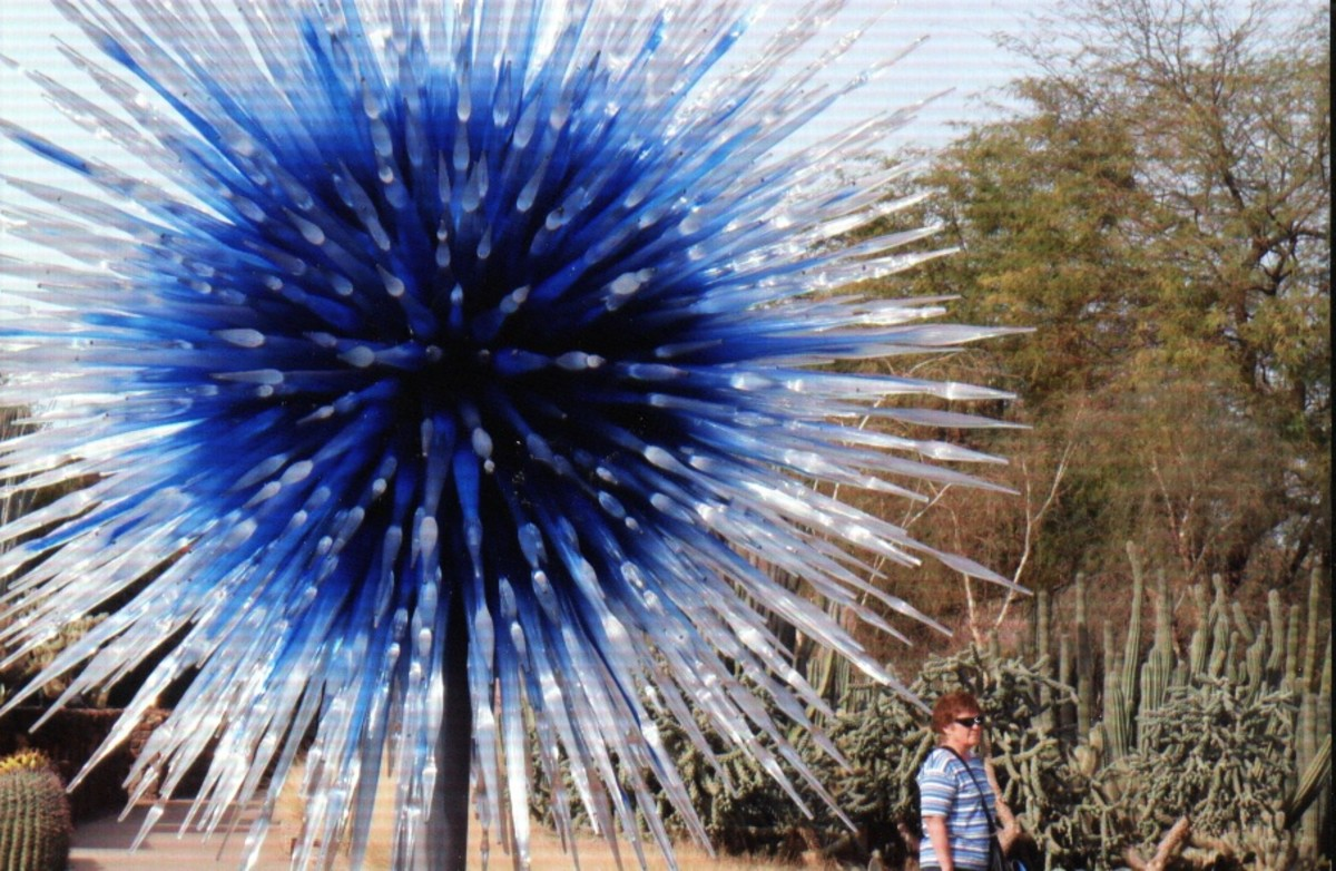 "A beautiful sculpture resembling an exploding blue star - ""Scarlet and Yellow Asymmetrical Towers"" at the entrance to Desert Discovery Loop"