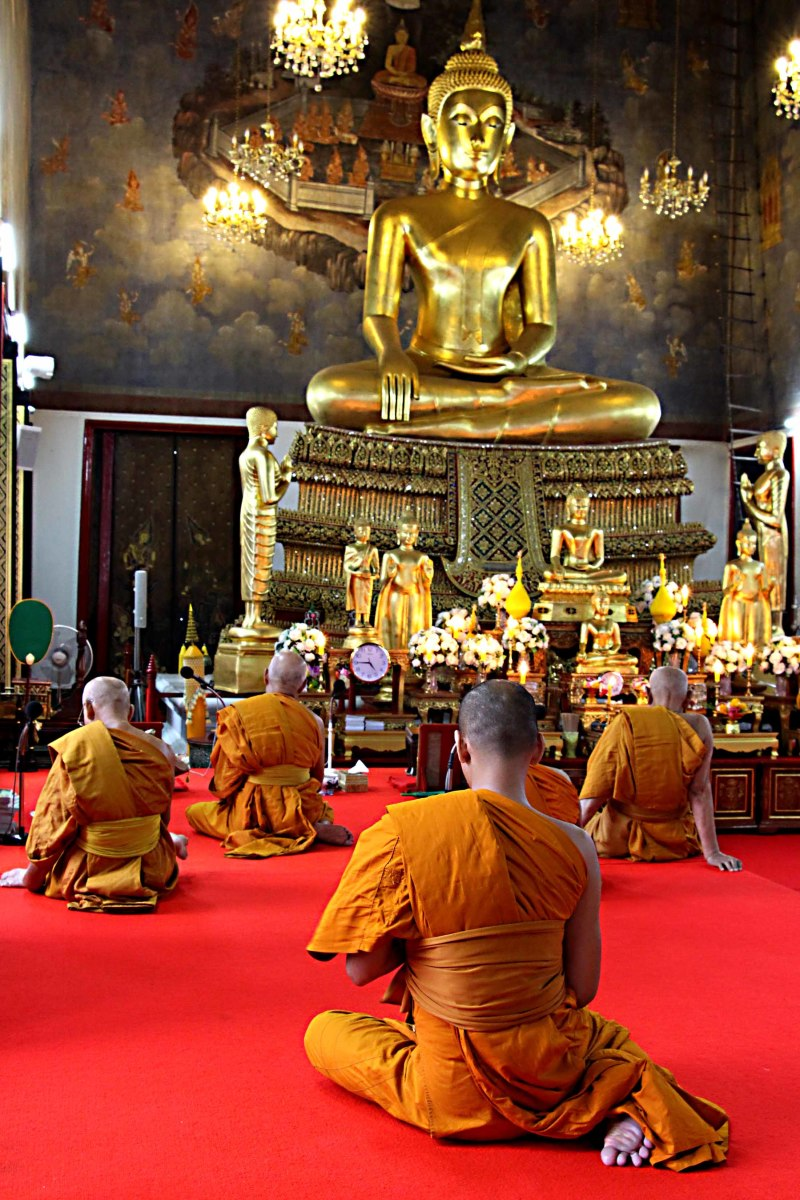 One of Bangkok's impressive temples, with monks at worship before Buddha