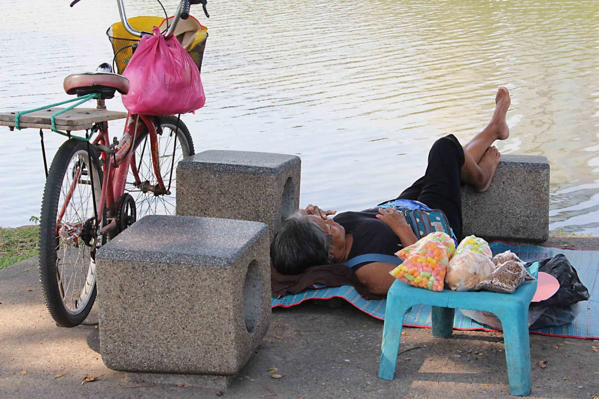 A cyclist finds sunbathing less exhausting than cycling in Lumpini Park