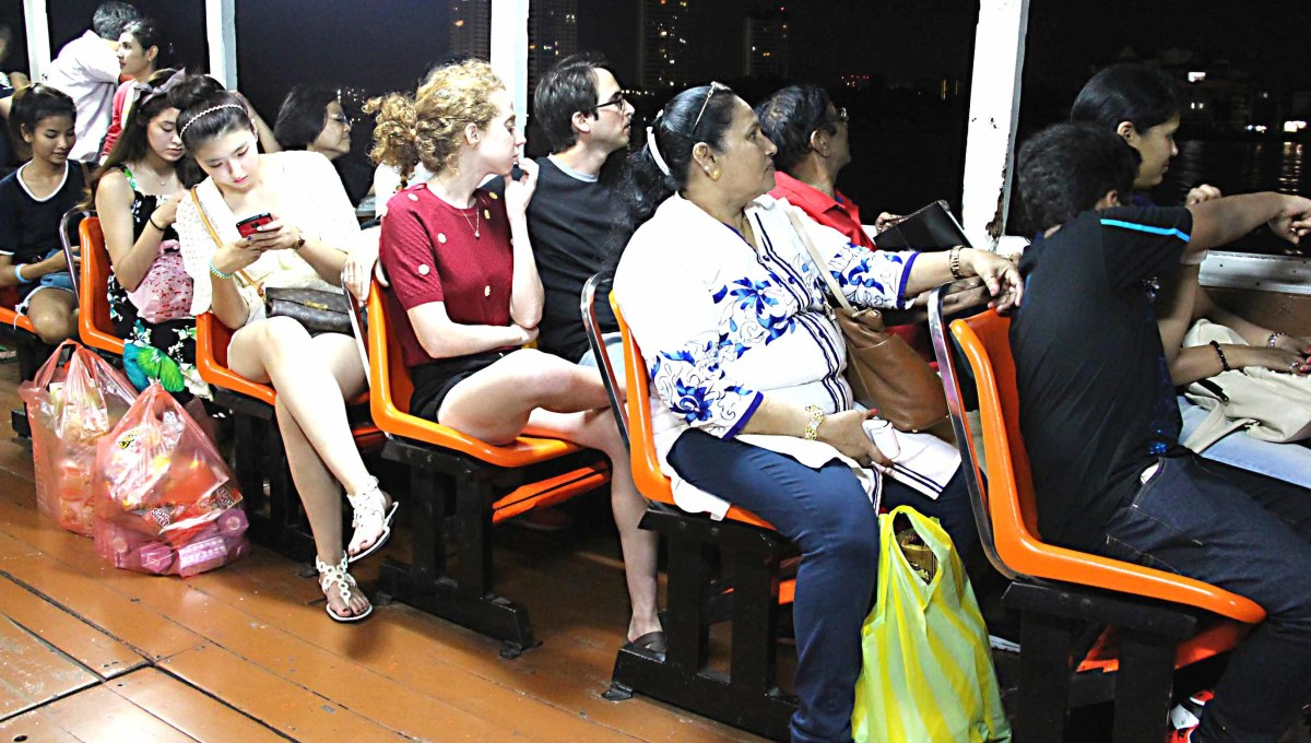 Thais and foreigners - known as 'farangs' - return from the night market and restaurant complex of Asiatique, on one of the Chao Phraya Express River Boats