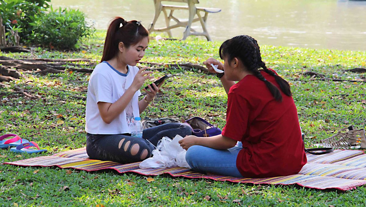 A couple of girls share a picnic in the park