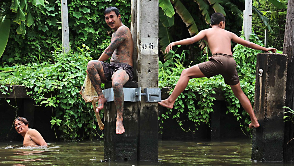 Men cooling off with a swim in one of the khlongs (canals) in West Bangkok