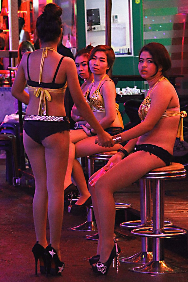 Bar girls at Soi Cowboy. Here a string of neon-lit clubs - many of which present revealing shows - will have scantily dressed girls on the street to draw the customers in for shows or drinks - or to ply whatever other business they may have in mind