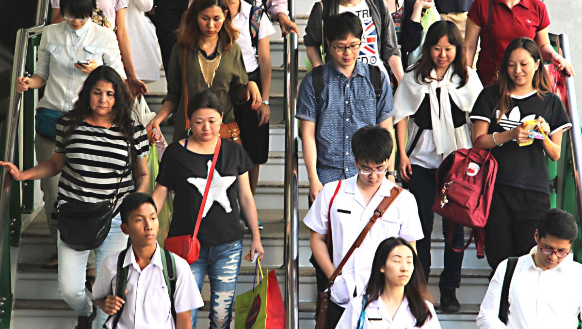 Daily commuting - the Skytrain is one of the most popular transport systems in the city. These commuters and shoppers are descending from a station above the streets