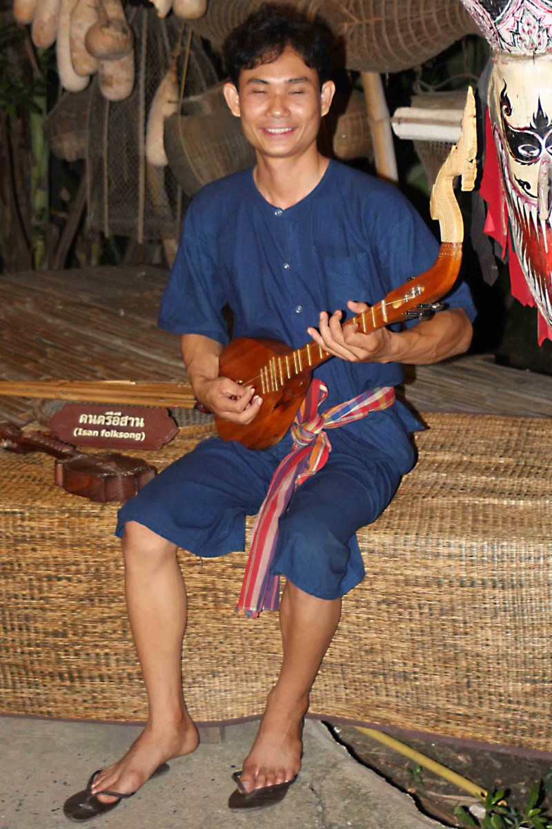 A musician with a 'phin' - a three-stringed guitar-like instrument