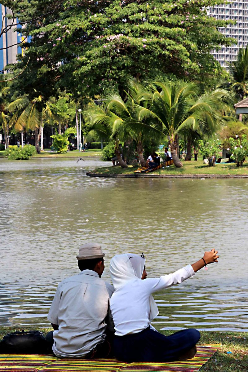 A Muslim couple relax in Chatuchak Park as the woman takes a phone selfie