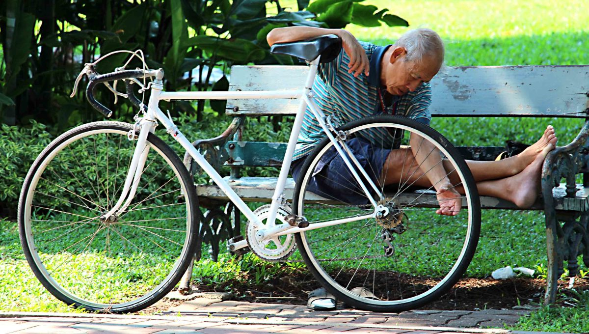 Another cyclist takes a rest and attends to his bicycle in Lumpini Park