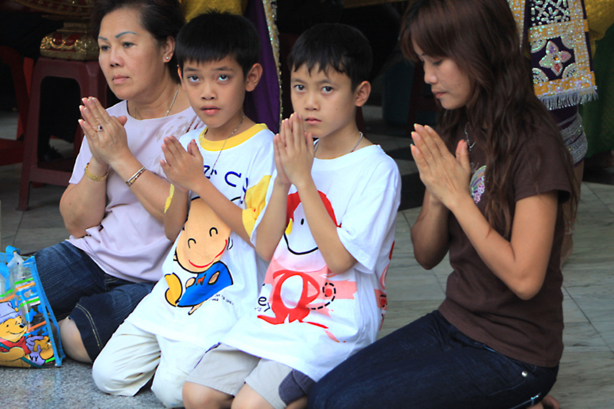 A moment of peaceful contemplation for a family at the Erawan Shrine