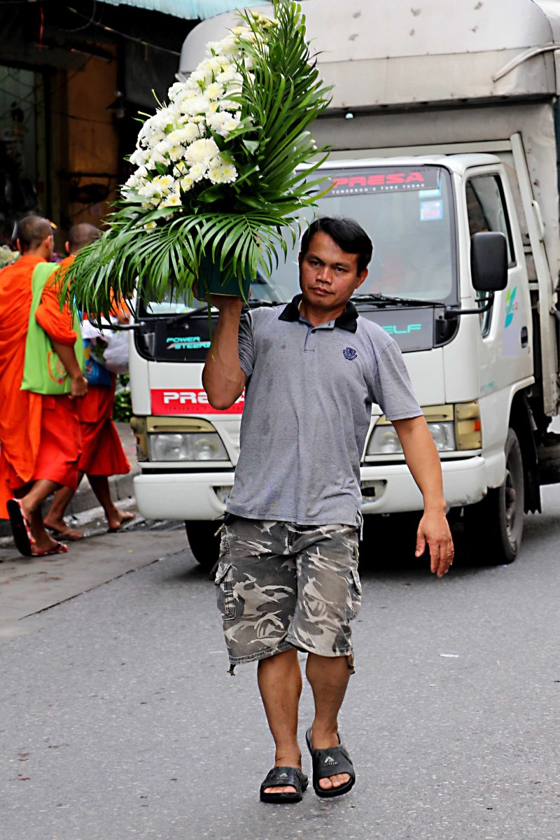 Two monks walk in the background, whilst a flower seller walks down the middle of the street with an impressive display - just 3 of the 8 million people of this great city