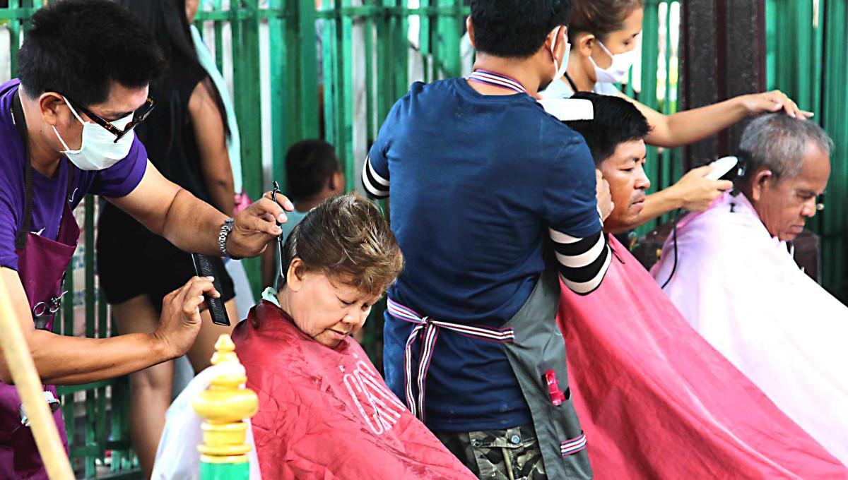 Open air hairdressing at Hua Lamphong Train Station, photographed on the platform of Bangkok's main nationwide terminus
