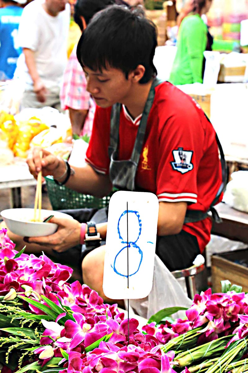 A flower seller pauses to enjoy lunch. The flowers are that most traditional of Thailand blooms - pink-purple orchids