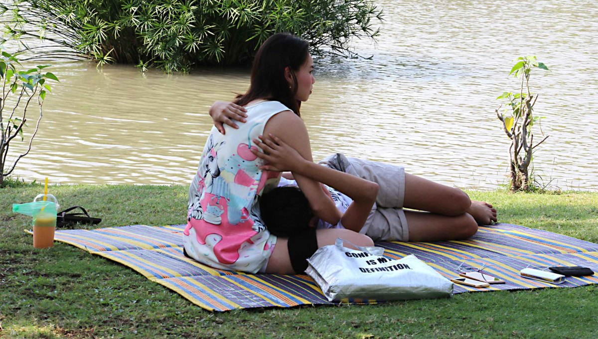 A couple embrace by the lake in Chatuchak Park