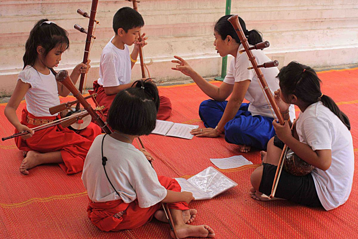 School children rehearse traditional Thai instruments during a music lesson in the grounds of the Wat Arun temple