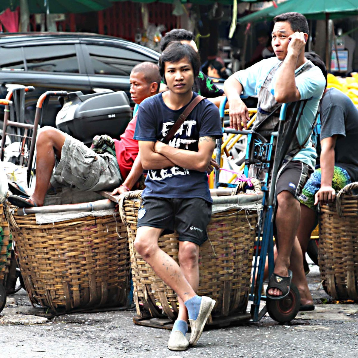 Market delivery men take a breather from ferrying goods in their giant baskets