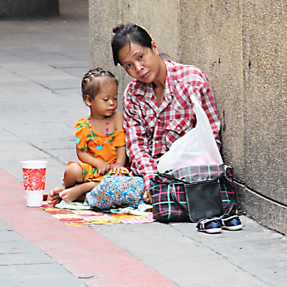 A young mother and child reduced to begging in the streets of Bangkok