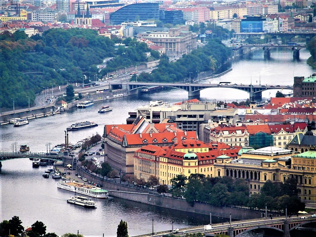 InterContinental Hotel behind the red-roofed buildings on the banks of the River Vltava..
